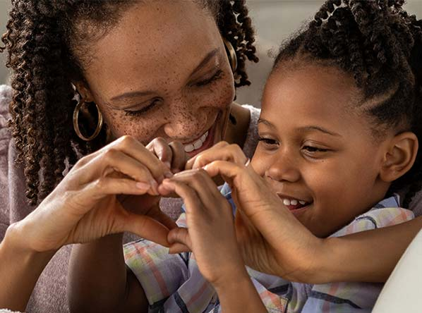 Mom and child making a heart with their hands
